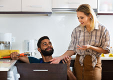 Specialist fixing leaky faucet, pleased cheerful blonde Royalty Free Stock Images