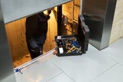 Specialist het bevestigen of het aanpassen liftmechanisme in lift schaft Regelmatig reparatie, de dienst en onderhoud van lift stock foto