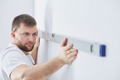 Specialist in home renovation. Male specialist in home renovation checking the wall with spirit level royalty free stock image