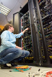 IT specialist installing cables in datacenter Stock Photo