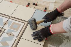 Specialist for laying tiles aligns the tiles with a carpenter`s. Hammer in the living room of a city apartment Stock Photos