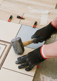 Specialist for laying tiles aligns the tiles with a carpenter`s. Hammer in the living room of a city apartment Royalty Free Stock Photo