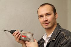Specialist makes repairs. Using drill. Make repairs Stock Photography