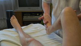 Specialist is making a massage to disabled person stock video footage