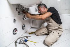 Specialist male plumber repairs faucet in bathroom. Male man dirty muscle inflated worker specialist plumber in black t-shirt and white old shabby working suit Stock Images