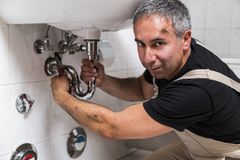 Specialist male plumber repairs faucet in bathroom. Male man smiling dirty muscle inflated worker specialist plumber in black t-shirt and white old shabby Stock Photography
