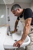 Specialist male plumber repairs faucet in bathroom. Male man dirty muscle inflated worker specialist plumber in black t-shirt and white old shabby working suit Stock Photo