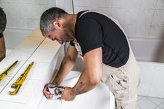 Specialist male plumber repairs faucet in bathroom. Male man dirty muscle inflated worker specialist plumber in black t-shirt and white old shabby working suit Royalty Free Stock Photo