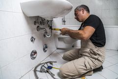 Specialist male plumber repairs faucet in bathroom. Male man dirty muscle inflated worker specialist plumber in black t-shirt and white old shabby working suit Stock Photos