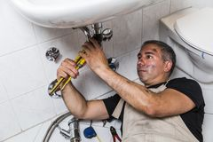 Specialist male plumber repairs faucet in bathroom. Male man dirty muscle inflated worker specialist plumber in black t-shirt and white old shabby working suit Royalty Free Stock Images
