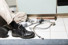 Specialist male plumber repairs faucet in kitchen. Male man worker specialist plumber in white dirty shabby working suit, black boots sitting on kitchen floor Royalty Free Stock Photo