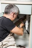 Specialist male plumber repairs faucet in kitchen. Male man young worker specialist plumber in white dirty old shabby working suit, black t-shirt sitting on the Stock Photography
