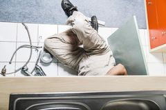 Specialist male plumber repairs faucet in kitchen. Male man young worker specialist plumber in white dirty old shabby working suit, black boots lyes on kitchen Royalty Free Stock Images