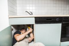 Specialist male plumber repairs faucet in kitchen. Male man young worker specialist plumber in white dirty old shabby working suit, black t-shirt lyes on the Royalty Free Stock Photography