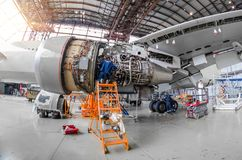 Specialist mechanic repairs the maintenance of a large engine of a passenger aircraft in a hangar. Stock Photos