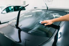 Specialist prepairs the window, car tinting film. Male specialist prepairs the window, car tinting film installation process, installing procedure Royalty Free Stock Photo