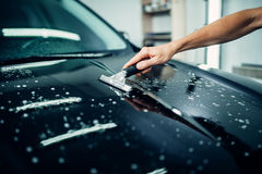 Specialist prepares car for protect against chips. And scratches. Paint protection. Protective coating Royalty Free Stock Photography