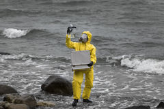 Specialist in protective suit  with case and container on rocky shore Royalty Free Stock Photos