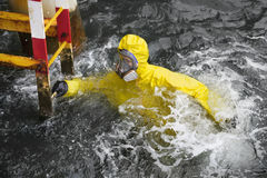 Specialist in sea water trying to reach ladder to save his life. Worker in professional, protective suit in ocean water trying to reach ladder to save his life royalty free stock photo