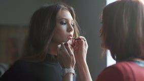 Specialist som gör makeup för modell I kulisserna av modebransch arkivfilmer