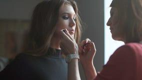 Specialist som gör makeup för modell Kantglansapplikation arkivfilmer