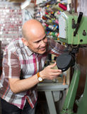 Specialist stitching shoes. Happy man stitching shoes on leather sewing machine at factory Stock Photography