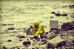 Specialist taking sample of water to container on rocky shore Stock Photography