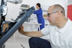 Specialist technician repairs photocopier in business office. Specialist technician repairs a photocopier in a business office Royalty Free Stock Photography
