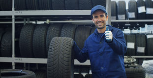 Specialist tire fitting in the car service, checks the tire and rubber tread for safety. Concept: repair of machines,. Fault diagnosis, repair specialist Royalty Free Stock Photo