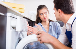 Specialist with tools and woman. Specialist in uniform with tools and housewife washing machine royalty free stock photos