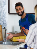 Specialist in uniform fixing leaky faucet, pleased blonde Stock Image