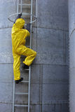 Specialist in uniform going up a metal ladder. Specialist in protective uniform going up a metal ladder on large industrial  silo in the plant Royalty Free Stock Photos