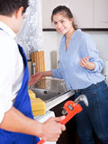 Specialist in uniform helping worried woman. Specialist in uniform helping young women to fix leaky faucet Stock Photo