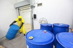 Specialist in uniform rolling barrel of chemicals. Worker in protective uniform,mask,gloves and boots rolling barrel of chemicals stock image