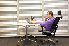 Specialist working with laptop in relaxed position with legs on tesk Royalty Free Stock Photography
