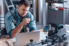 Specialist working in manufacturing plant. Specialist in machine construction working in manufacturing plant at desk with laptop and equipment royalty free stock photos