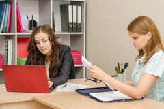 The specialist works in the laptop, the visitor leafing through paper documents Royalty Free Stock Photo