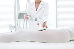 Specialista alto vicino di bellezza che fa massaggio dell'apparecchiatura di GPL sulle anche femminili immagine stock