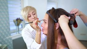 Specialista de salon de beauté faisant le maquillage et la coiffure professionnels pour la jeune femme de brune banque de vidéos