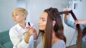 Specialista de salon de beauté faisant le maquillage et la coiffure professionnels pour la jeune femme de brune clips vidéos
