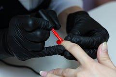 Specialista del manicure nelle cure nere dei guanti circa le unghie delle mani Il manicure dipinge le unghie con smalto rosso immagini stock libere da diritti