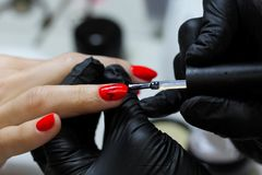 Specialista del manicure nelle cure nere dei guanti circa le unghie delle mani Il manicure dipinge le unghie con smalto rosso immagini stock