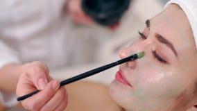 Specialista di cosmetologia che applica maschera facciale facendo uso della spazzola, facendo pelle idratata e sana donna di dist video d archivio