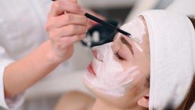 Specialista di cosmetologia che applica maschera facciale facendo uso della spazzola, facendo pelle idratata e sana donna di dist archivi video