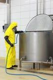 Specialista in uniforme con il tubo flessibile in fabbrica Fotografia Stock