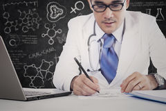 Specialistdoktorn skriver medicinrecept Royaltyfri Fotografi