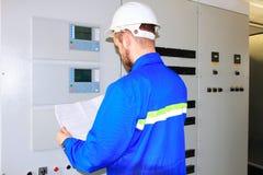 Specialisten av det industriella komplexet ser teckningen av den elektriska strömkretsen Fotografering för Bildbyråer