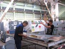 Specialisten för arbetemannen samlar flygplandelar på flygplanfabriken Chkalov Novosibirsk royaltyfria bilder