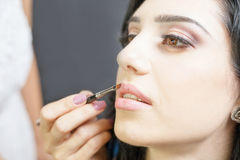 Specialisten i skönhetsalong får läppstift, kantglansen, yrkesmässigt smink Arkivbilder