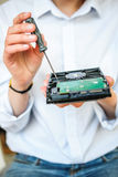 It-specialisten räcker hållande HDD med skruvmejsel Royaltyfria Bilder